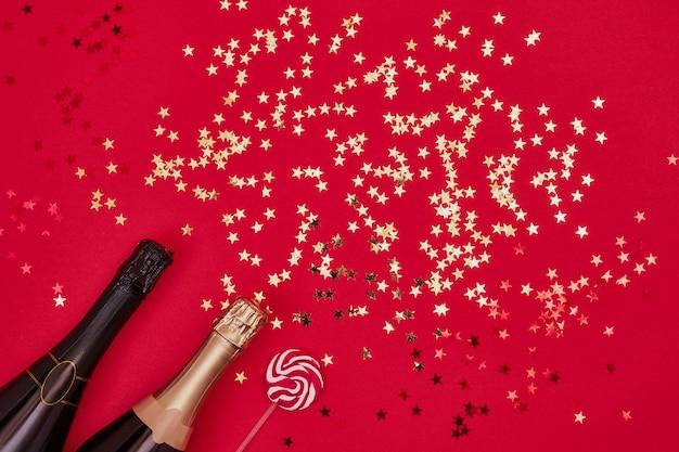 Sektflasche mit goldenen konfetti auf rotem grund. exemplar, ansicht von oben, flach zu legen