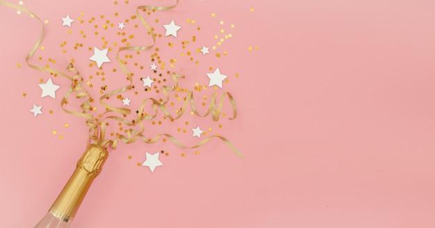 Sektflasche mit konfettisternen und goldenen parteiausläufern auf rosa abstraktem hintergrund. neujahr, weihnachten, geburtstag oder hochzeitskonzept. oberes horizontales ansicht copyspace ebenenlage.