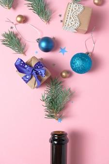 Sektflasche mit unterschiedlicher weihnachtsdekoration auf rosa