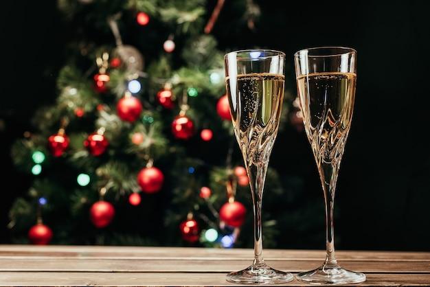 Sektgläser auf dem hintergrund eines geschmückten weihnachtsbaums. neujahr