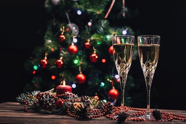 Sektgläser auf weihnachtlichem hintergrund mit einem geschmückten weihnachtsbaum und einer girlande