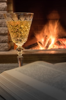 Sektglas und ein aufgeschlagenes buch gegen gemütlichen kamin.
