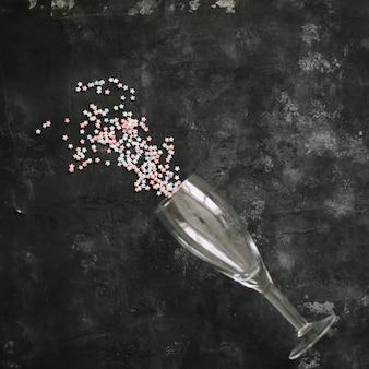 Sektglas voller farbiger glitzer auf dunklem hintergrund kreatives minimalistisches partykonzept