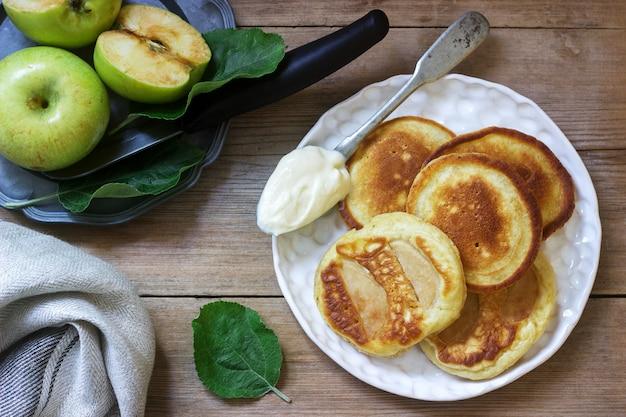 Selbst gemachte apfelstückchen mit sauerrahm, kaffee und grünen äpfeln auf einem holz