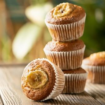 Selbst gemachte bananenmuffins in einem stapel auf einem holztisch. gesunder veganer nachtisch.