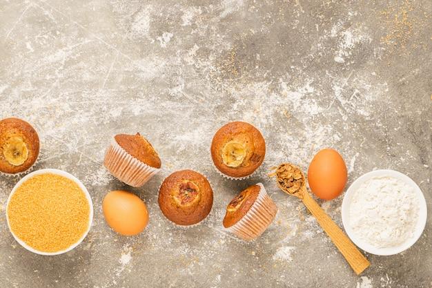 Selbst gemachte bananenmuffins und kochen die bestandteile, die auf einem grauen hintergrund ausgebreitet werden. gesunder veganer nachtisch.