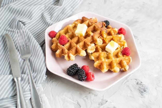 Selbst gemachte belgische waffeln mit butter honey berries raspberries blackberries table-geschirrtuch-rosa-platten-morgen-frühstück