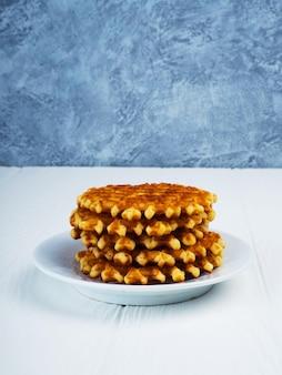 Selbst gemachte belgische waffeln mit puderzucker auf schwarzem hintergrund, sehr geschmackvoller snack.