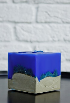 Selbst gemachte blaue kerze mit beton auf der oberfläche einer weißen wand