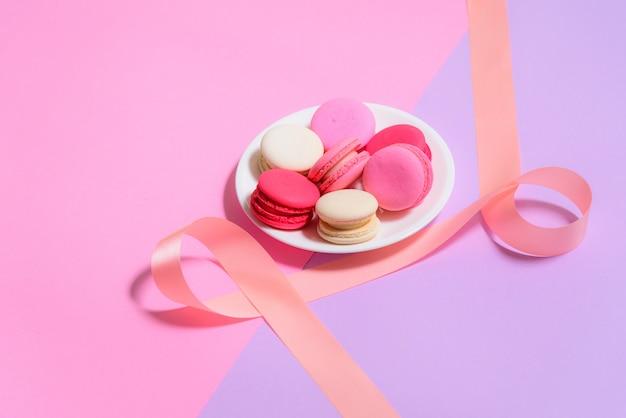 Selbst gemachte bunte makronen oder macaron auf weißer platte auf rosa und purpurrotem hintergrund