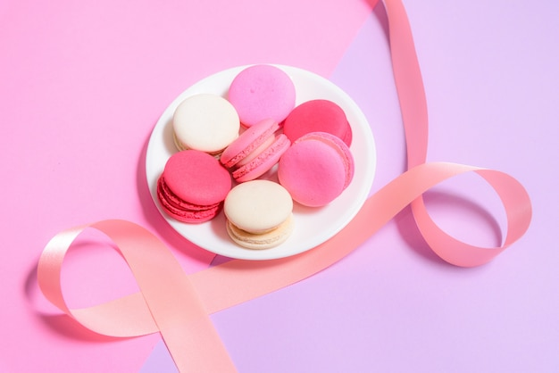 Selbst gemachte bunte makronen oder macaron auf weißer platte mit copyspace auf rosa und purpurrotem hintergrund