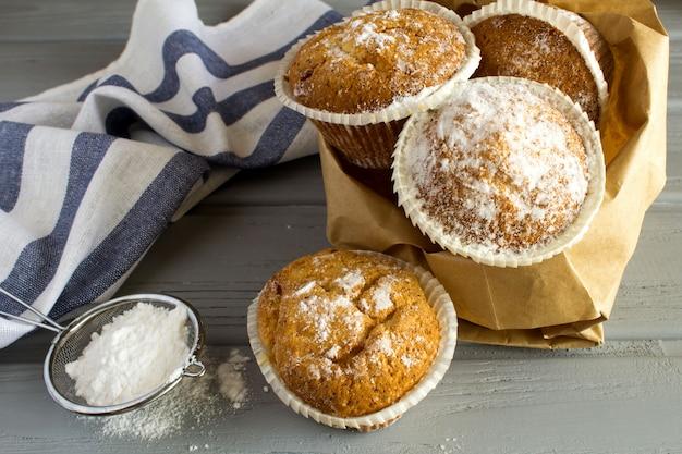 Selbst gemachte cupcakes mit puderzucker auf dem grauen hölzernen hintergrund