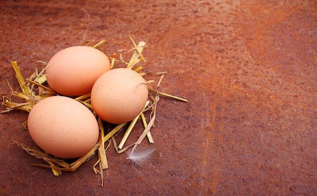 Selbst gemachte eier in einem strohhalm auf einem alten hintergrund.