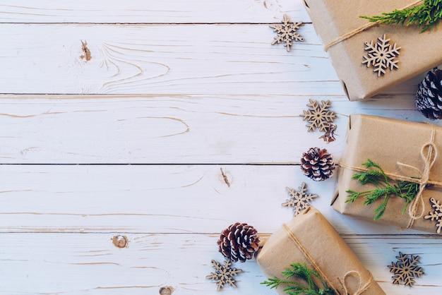 Selbst gemachte eingewickelte weihnachtsgeschenkbox stellt sich auf einem hölzernen tabellenhintergrund dar.