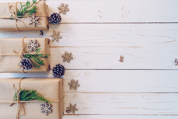 Selbst gemachte eingewickelte weihnachtsgeschenkbox stellt sich auf einem hölzernen tabellenhintergrund mit raum dar.