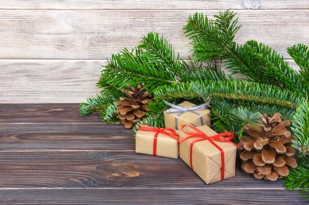 Selbst gemachte eingewickelte weihnachtsgeschenke auf holzoberfläche