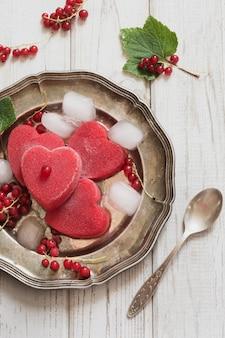 Selbst gemachte eiscreme der roten johannisbeere in form des herzens und auf weinleseteller und hölzernem hintergrund.