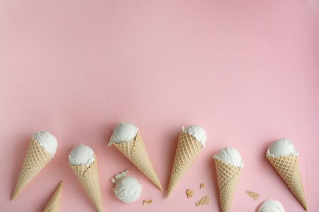 Selbst gemachte eiscreme in den kegeln einer waffel auf rosa hintergrund. exemplar für einen text