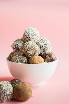 Selbst gemachte energiebälle, vegane schokoladentrüffel mit kakao, kokosnuss auf rosa