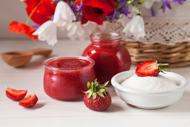 Selbst gemachte erdbeermarmelade im glasgefäß und korb mit sommerblumen auf dem holztisch