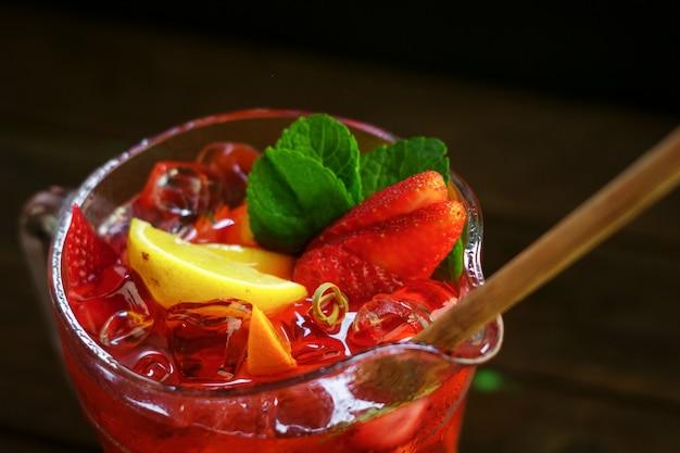 Selbst gemachte frische erdbeerlimonade mit frischer frucht in einem glas auf schwarzem hintergrund