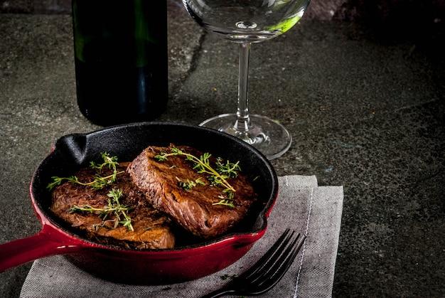 Selbst gemachte gegrillte rindfleischsteaks in einer portionierten pfanne, mit einer gabel, einem messer und einem glas wein auf schwarzem steintisch