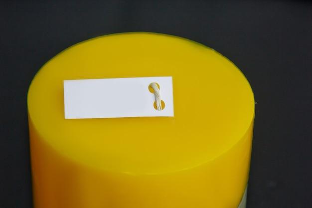 Selbst gemachte gelbe kerze mit beton auf einer schwarzen oberfläche