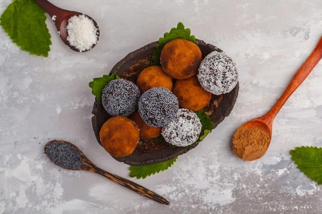 Selbst gemachte gesunde rohe energie-bälle des strengen vegetariers mit johannisbrotbaum, einer mohnblume und kokosnuss, draufsicht. gesundes veganes lebensmittelkonzept.