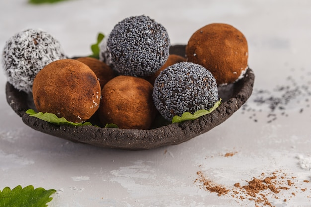 Selbst gemachte gesunde rohe energie-bälle des strengen vegetariers mit johannisbrotbaum, einer mohnblume und kokosnuss. gesundes veganes lebensmittelkonzept.