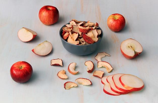 Selbst gemachte getrocknete äpfel mit frischen äpfeln auf einem hellen holztisch.