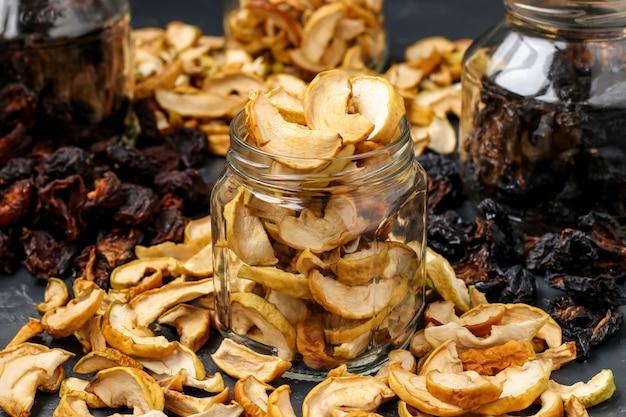 Selbst gemachte getrocknete äpfel, pflaumen und birnen in den glasgefäßen, horizontale orientierung, nahaufnahme