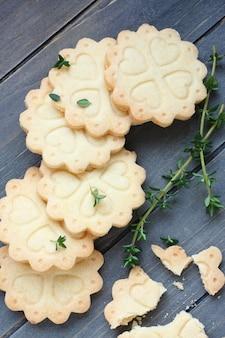 Selbst gemachte glutenfreie keksplätzchen mit niederlassungen des thymians auf altem hölzernem hintergrund