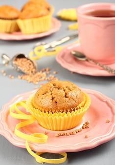 Selbst gemachte glutenfreie muffins vom buchweizenmehl auf rosafarbener platte