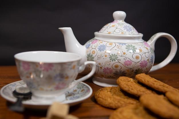 Selbst gemachte haferkekse mit einer tasse tee auf einem alten hölzernen hintergrund