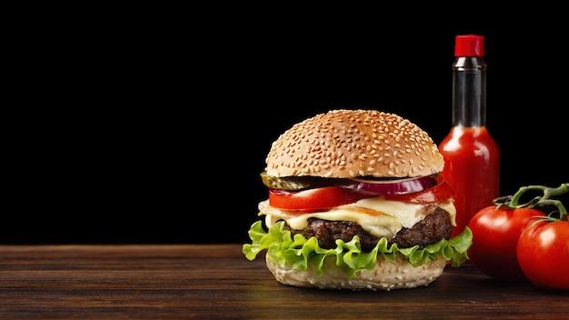 Selbst gemachte hamburgernahaufnahme mit flasche des rindfleisches, der tomate, des kopfsalates, des käses und der soße auf holztisch. fastfood auf dunklem hintergrund