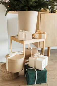 Selbst gemachte handwerkliche geschenkboxen mit fliegen unter weihnachtsbaum.