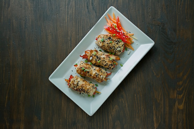 Selbst gemachte hühnerbrust rollt mit grüns, karottenscheiben, grünem pfeffer auf einer hellen rechteckigen platte.