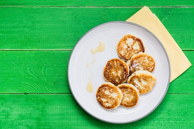 Selbst gemachte hüttenkäsepfannkuchen mit honig auf einer platte auf einem holztisch. ansicht von oben
