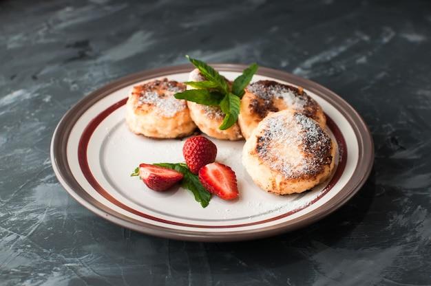 Selbst gemachte käsedonuts mit beerenmarmelade und erdbeeren