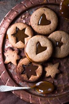 Selbst gemachte karamellplätzchen der sternform des weihnachtsneujahrs über holzhintergrund. flache lage, platz.
