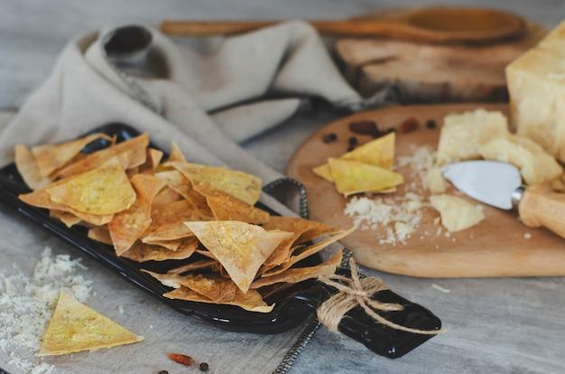 Selbst gemachte knusperige chips mit dem parmesankäseparmesankäse gemacht vom armenischen fladenbrotlavasch auf handcrafted platte