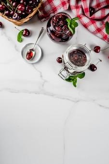 Selbst gemachte konservierte kirsch- und minzenmarmelade, mit frischen kirschen auf draufsicht des weißen marmorhintergrundes