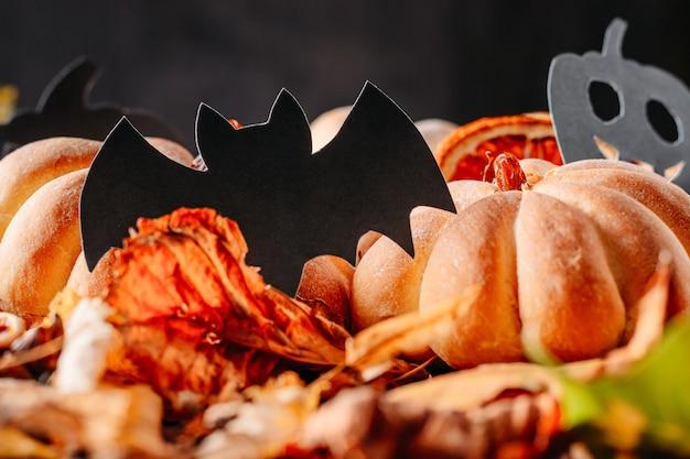 Selbst gemachte kuchen in form des halloween-kürbises mit herbstlaub auf dunkelheit