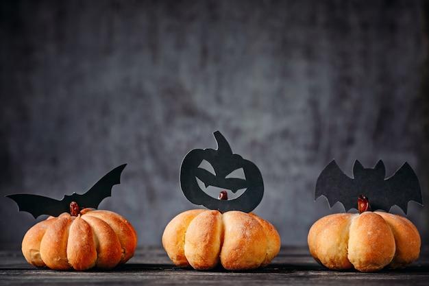 Selbst gemachte kuchen in form von kürbis- und halloween-dekorationen auf dunklem hintergrund