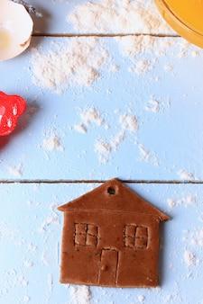 Selbst gemachte kuchen ingwerplätzchen-kleinen hauses weihnachten auf einer rustikalen art der hellen hölzernen hintergrundselektiven weichzeichnung