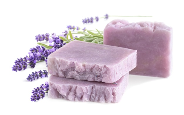Selbst gemachte lavendelseifenstücke mit lavendelblumenbündel lokalisiert auf einem weißen hintergrund