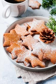 Selbst gemachte lebkuchenplätzchen der weihnachtssternform in der keramikplatte auf der alten grauen betonoberfläche. draufsicht