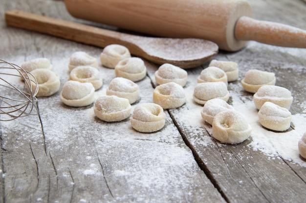 Selbst gemachte mehlklöße mit mehl und küchengeschirr auf rustikalem holztisch. traditionelle russische pelmeni. halbfertige produkte.