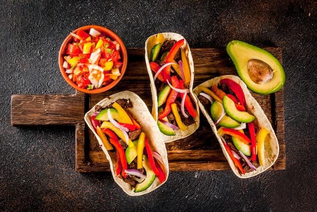 Selbst gemachte mexikanische schweinefleisch-tacos mit gemüse und salsa