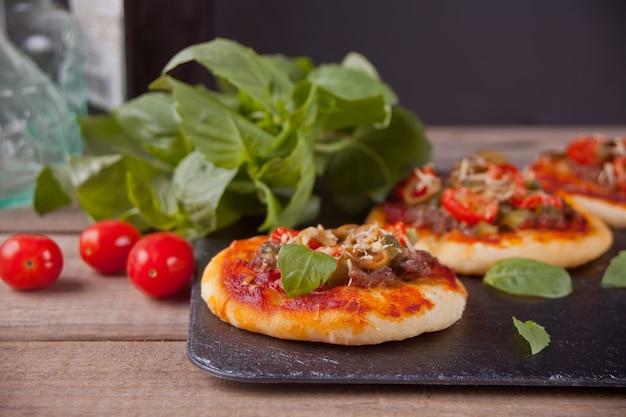Selbst gemachte minipizza auf dem schwarzblech.